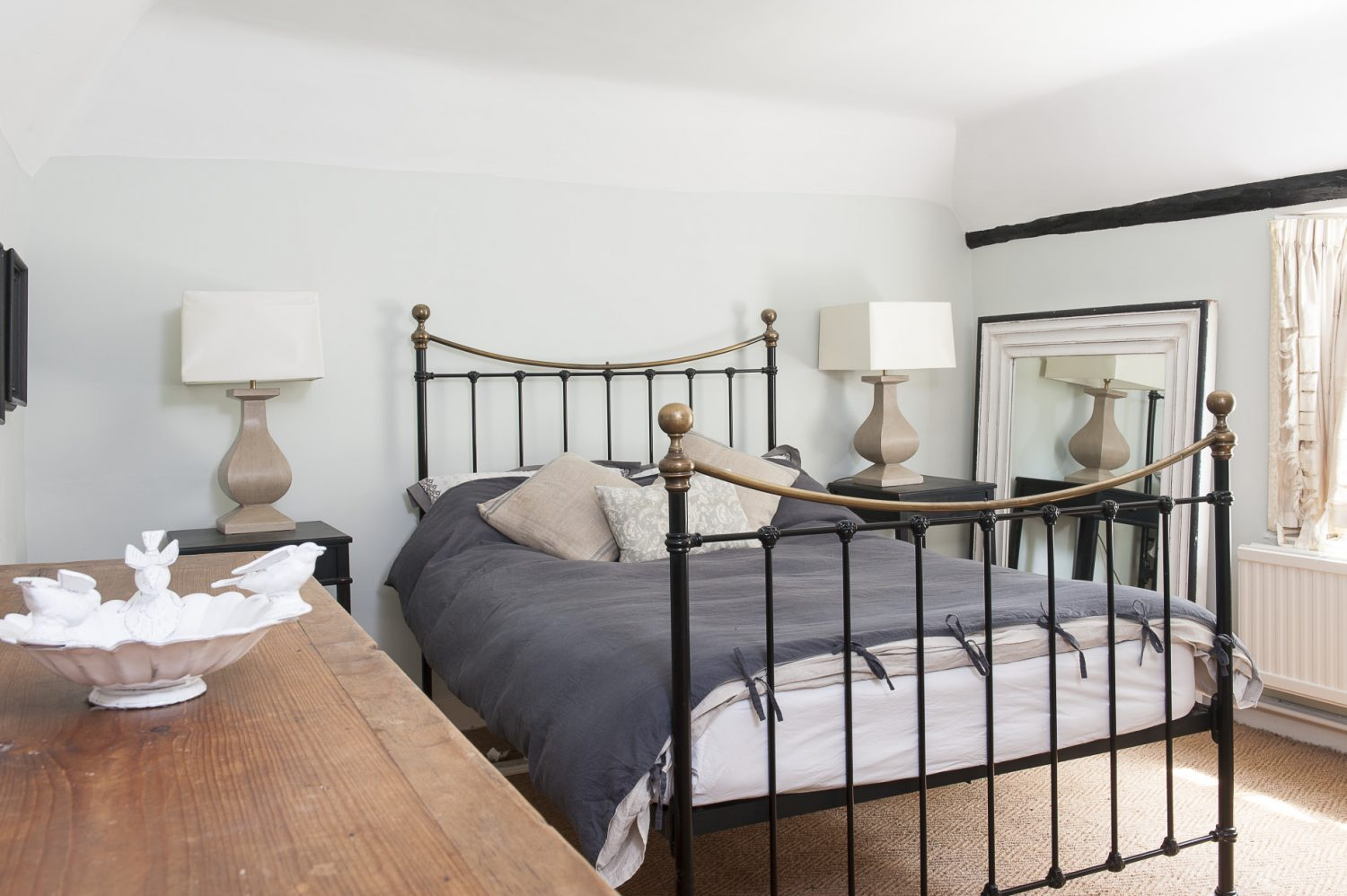 Another guest bedroom is furnished with a Victorian brass bed, along with matching side tables, stone table lamps and a large black and white-framed mirror from Homesense in Tunbridge Wells