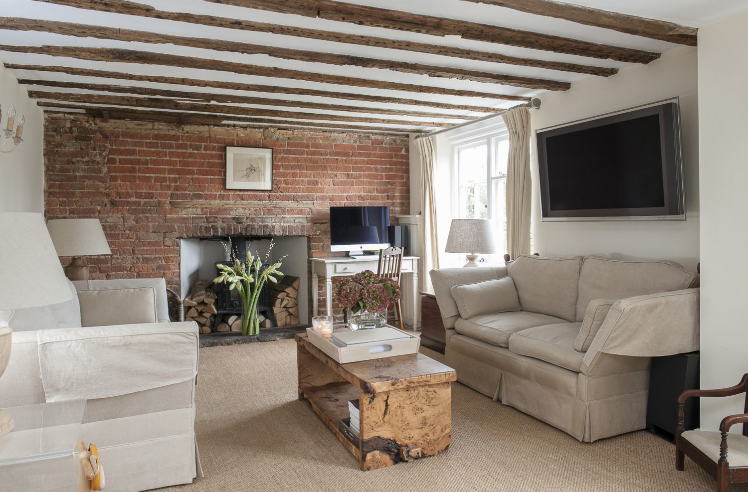 Holly and Chris kept the fireplace wall as bare brickwork and exposed the original beams
