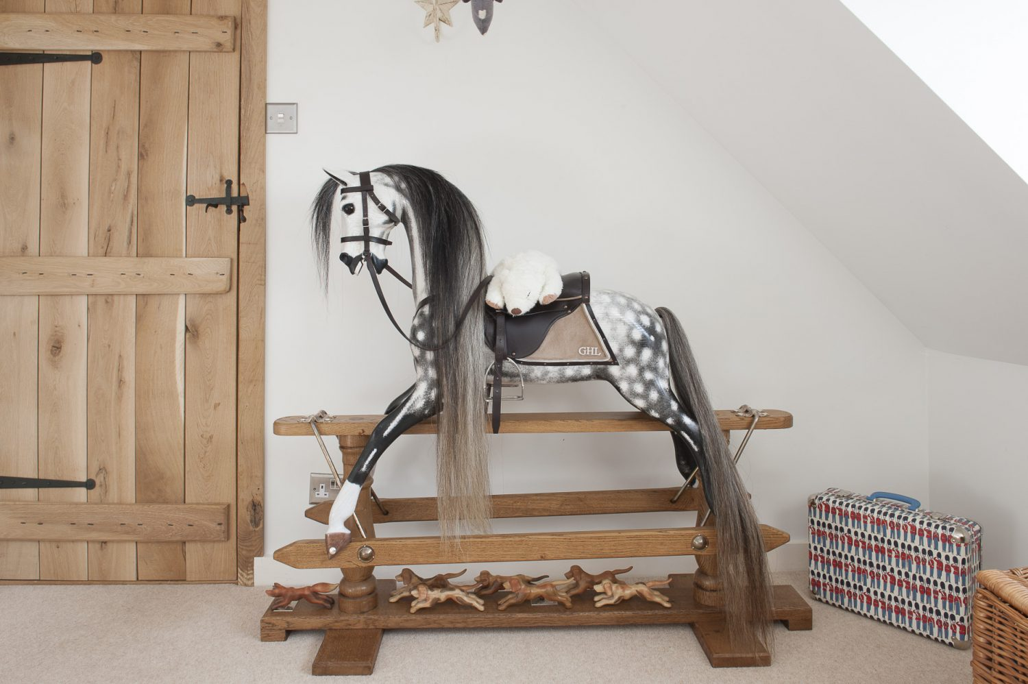 The blinds in George's room are made from Designers Guild fabric sourced from Bell House Fabrics in Cranbrook. His elegant dapple grey Stevenson Brothers rocking horse features little hounds running beneath it