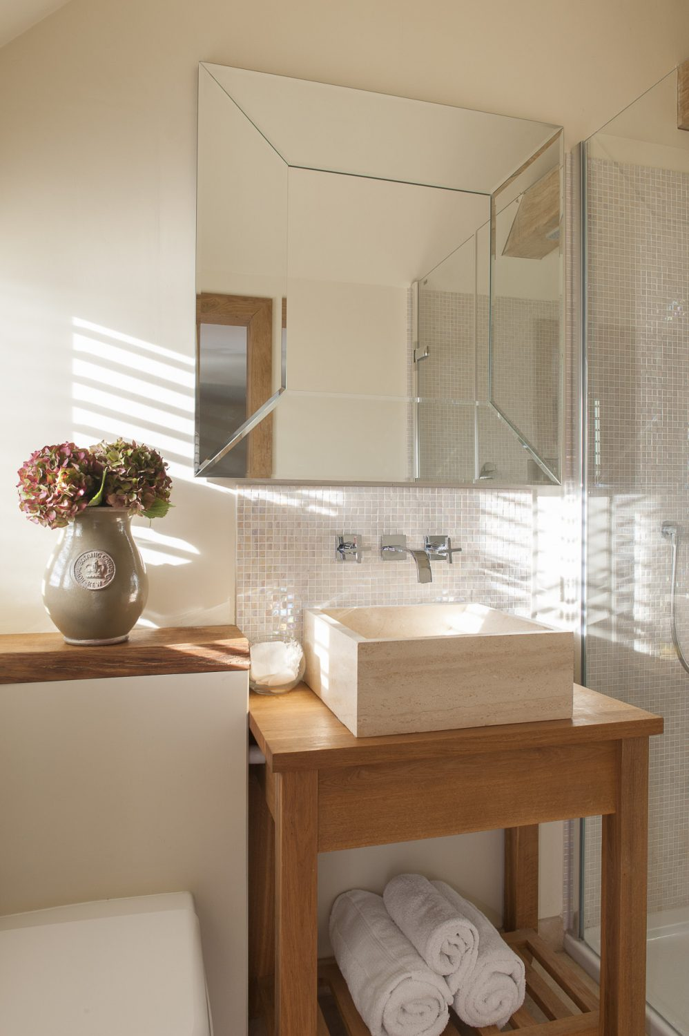 The en suite shower room could not be cooler – a lovely stone basin supported by a block of Chris's oak, a marvellous mirror from Woodcocks, tiny mother of pearl mosaic tiles from Fired Earth and travertine flooring