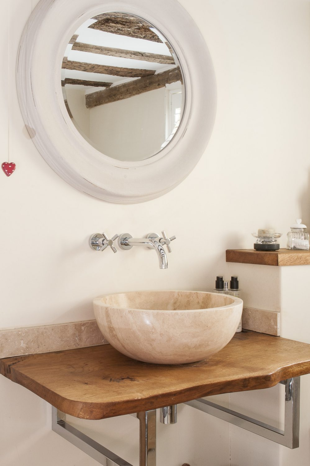 A stone bowl basin is supported by a polished oak table with chrome legs, made by Chris