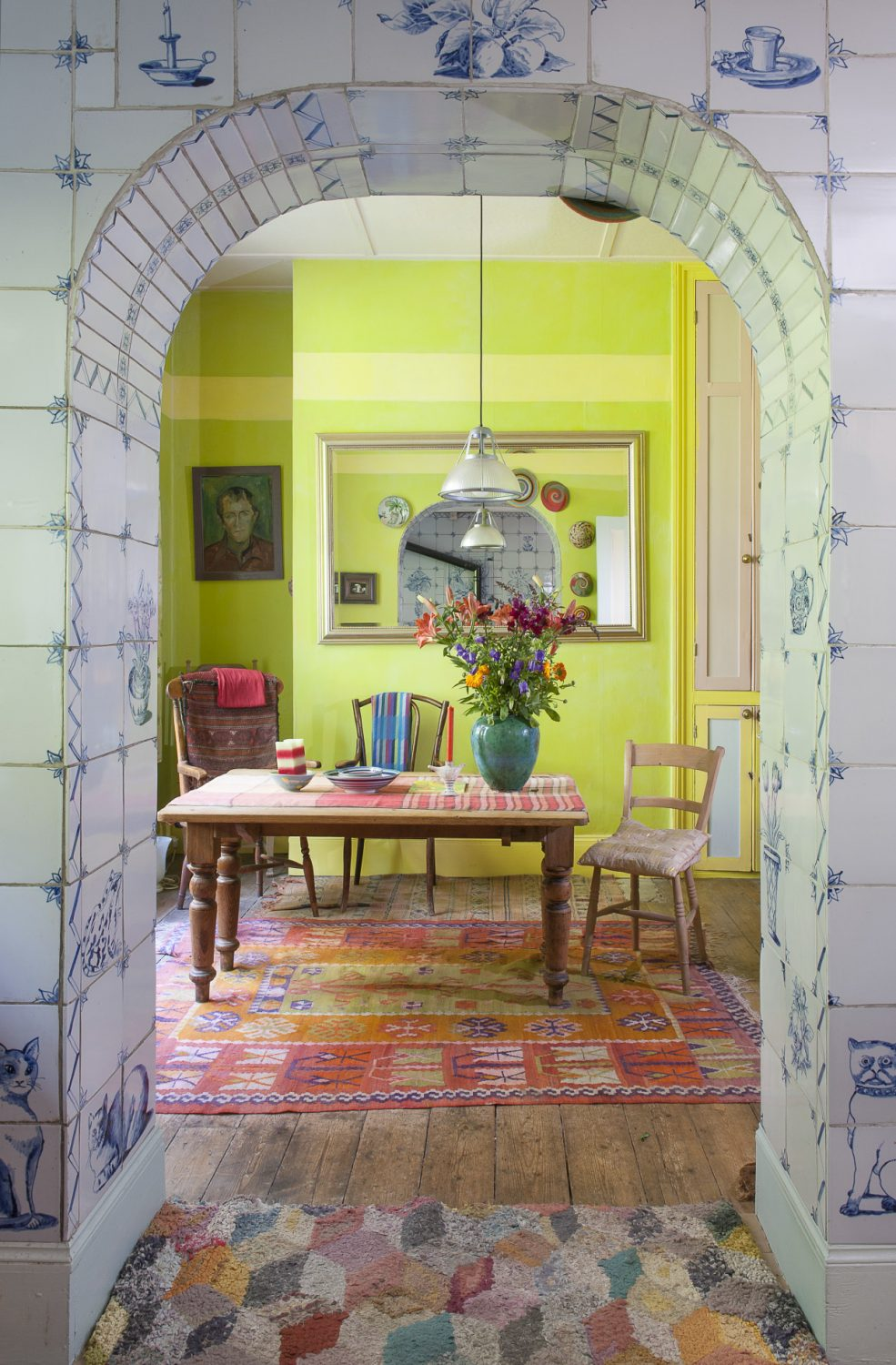 In the seating area of the kitchen, the walls are painted in vibrant shades of lime green accentuated by an intricate orange and red rug which sits under the table