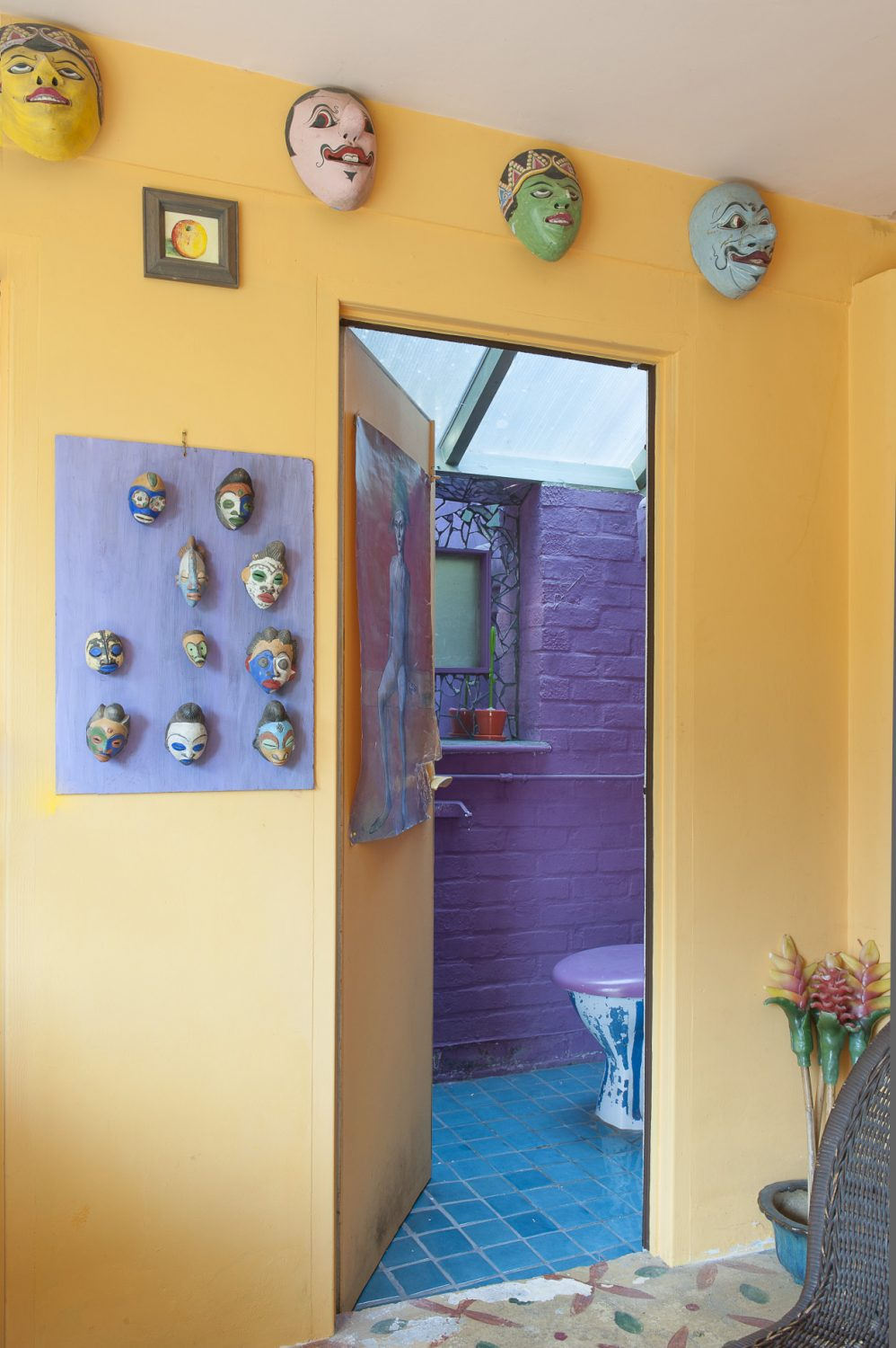 Behind a door in the vibrant garden room is the downstairs loo, painted a stunning purple and featuring a mosaic mirror. The orange walls are decorated with masks from Bali and South Africa