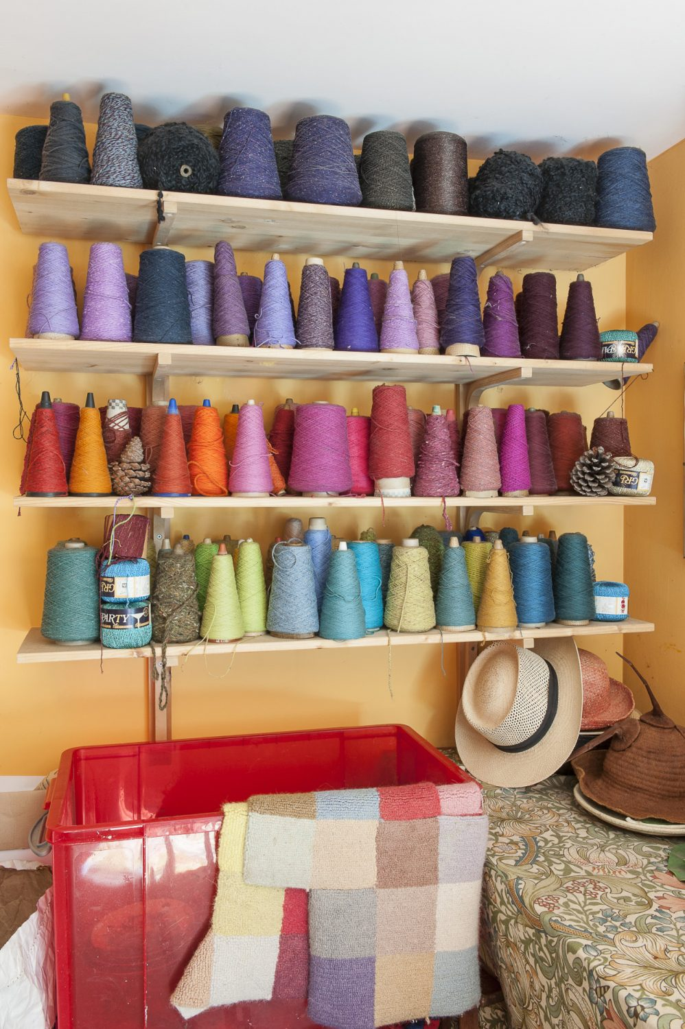 Coloured yarns are stacked in one corner in contrasting but complementary colours