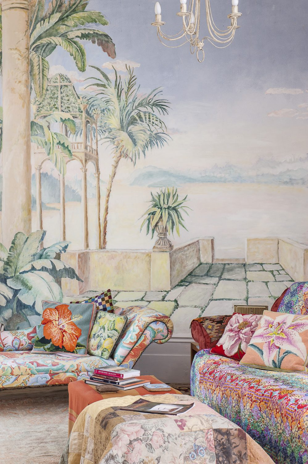 A plethora of needlepoint cushions with images of lilies, hibiscus and peonies, all worked by Kaffe, are scattered along the sofa and adjacent chaise longue