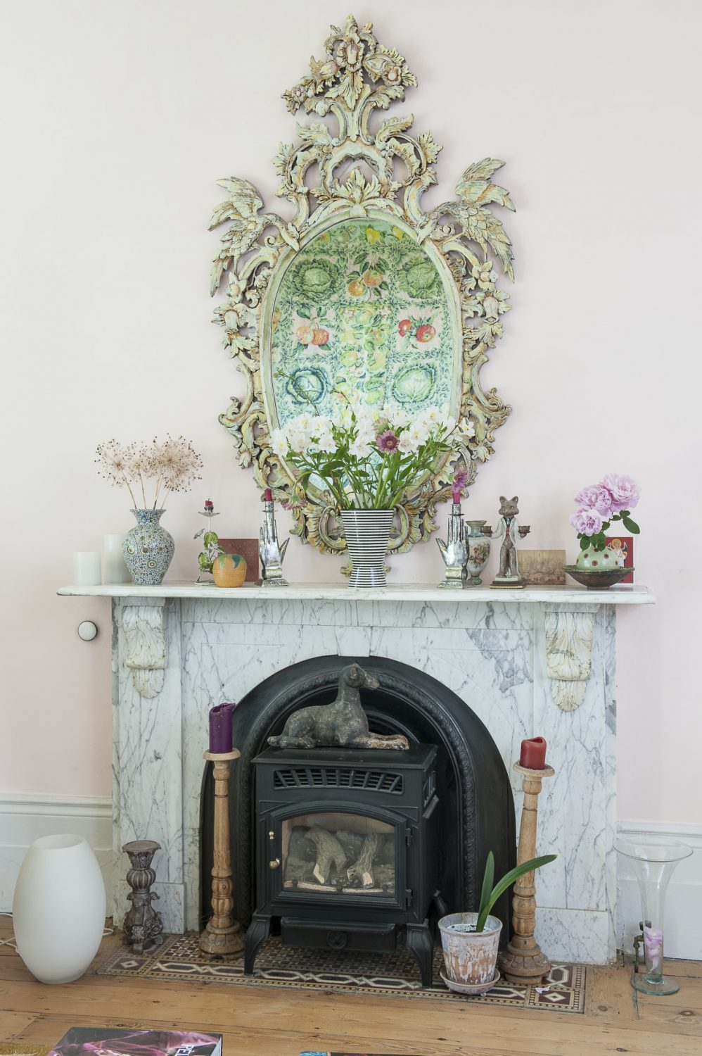 Kaffe's 'Cabbages and Apples' needlepoint is perfectly reflected in an ornate gilded mirror above the white marble fireplace