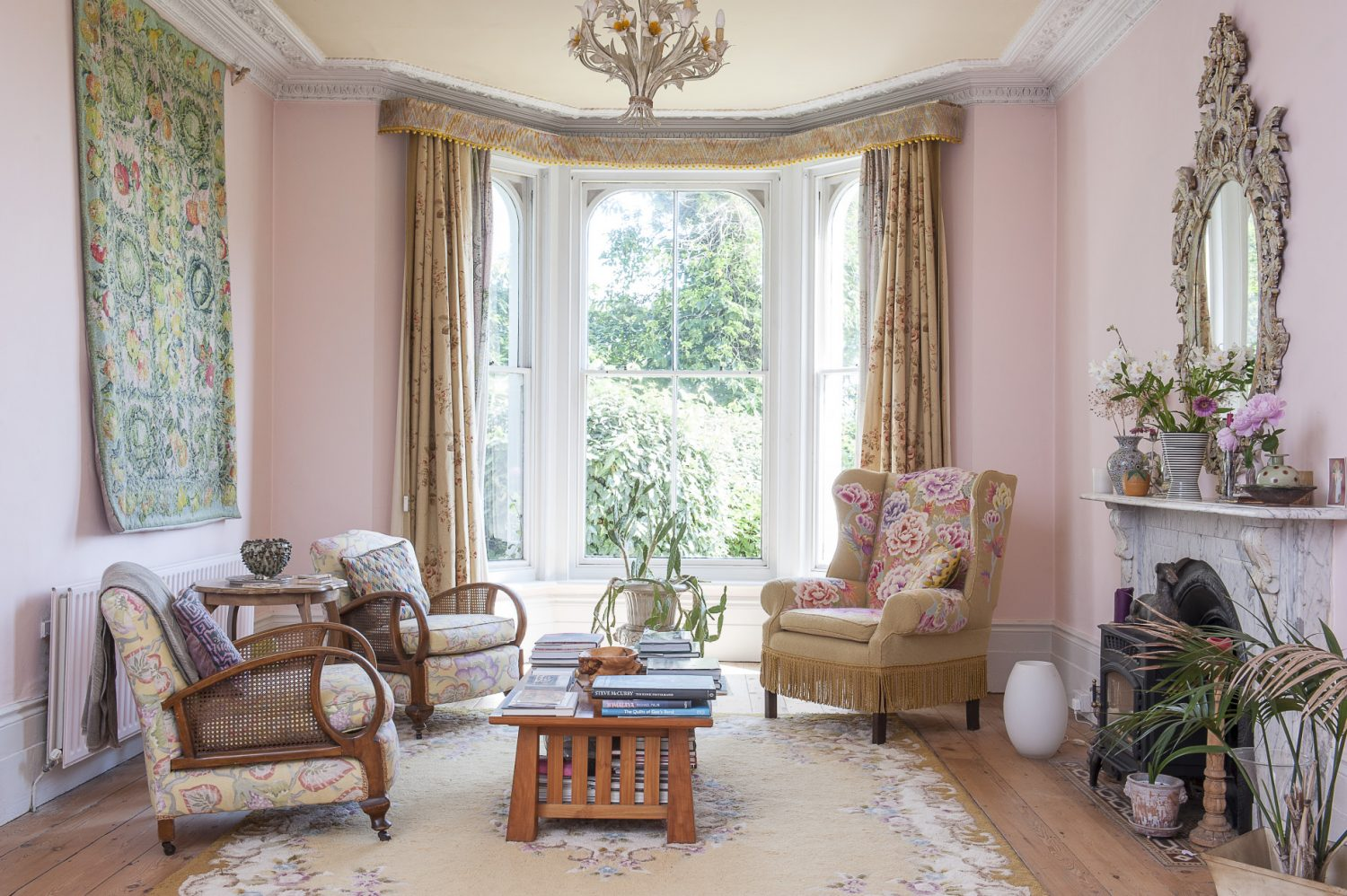 Two of the four easy chairs in the sitting room have been upholstered in needlepoint by Kaffe, continuing the floral theme. These blend perfectly with the honey-coloured floorboards which were here when Kaffe and Brandon moved in