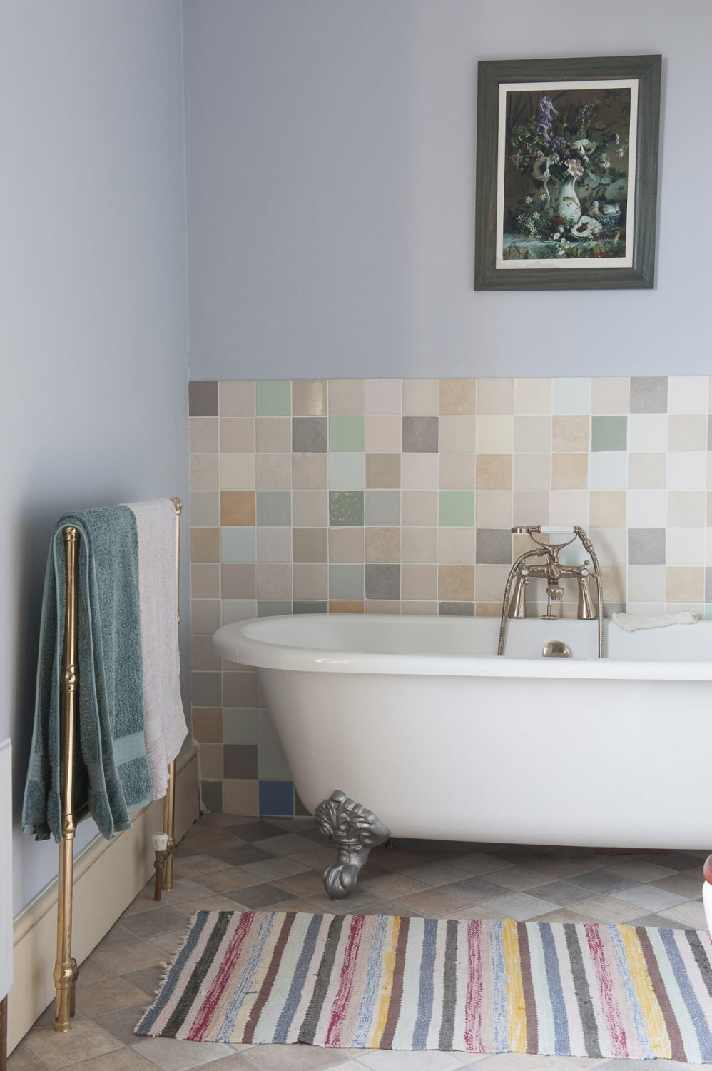In the bathroom, floor tiles in muted earthy tones complement the small square pastel wall tiles that run behind the freestanding bath and basin