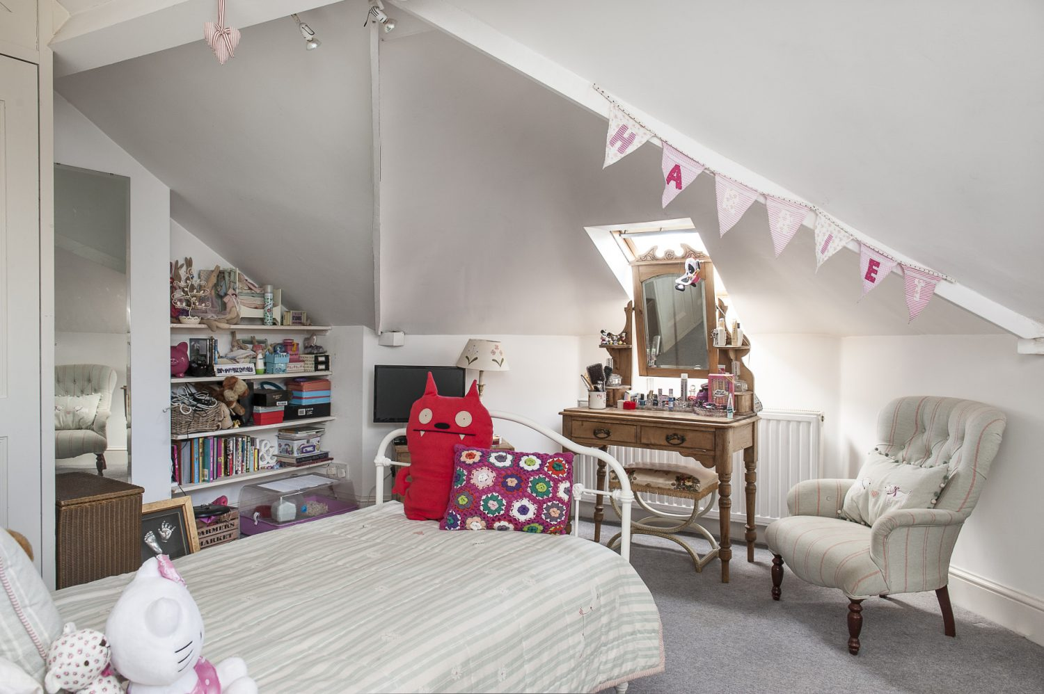 In the eaves is younger daughter Harriet's room which features pink bunting, an antique white iron bedstead with a Susie Watson coverlet and a Victorian pine dressing table