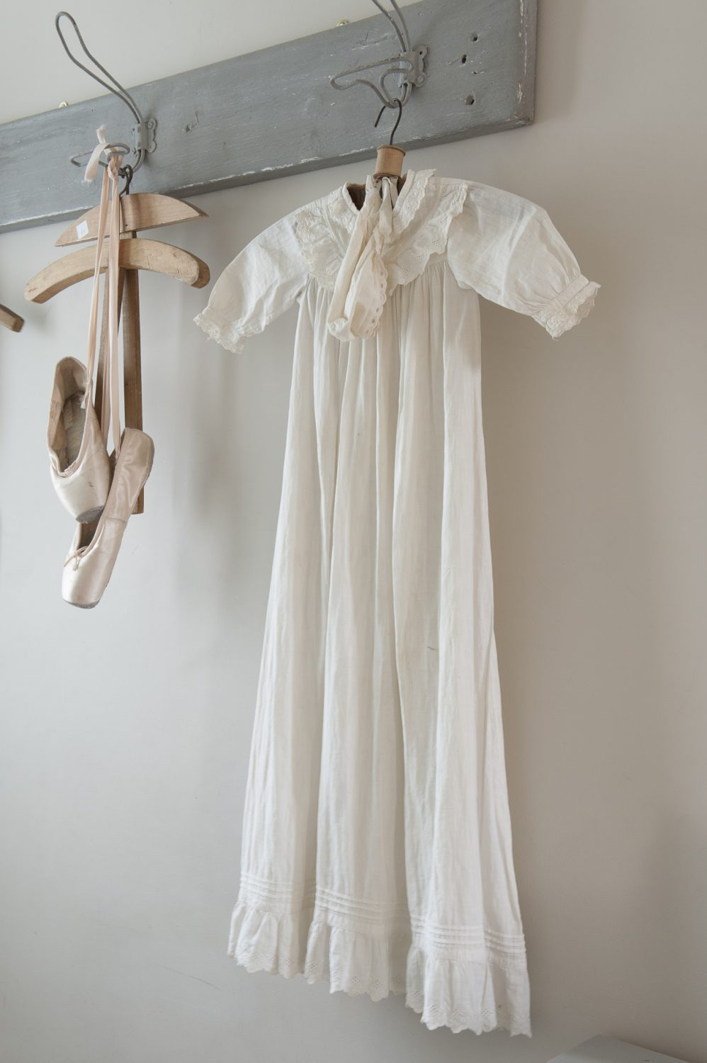 Bloch ballet shoes and a vintage christening robe hang on wire hooks by the front door