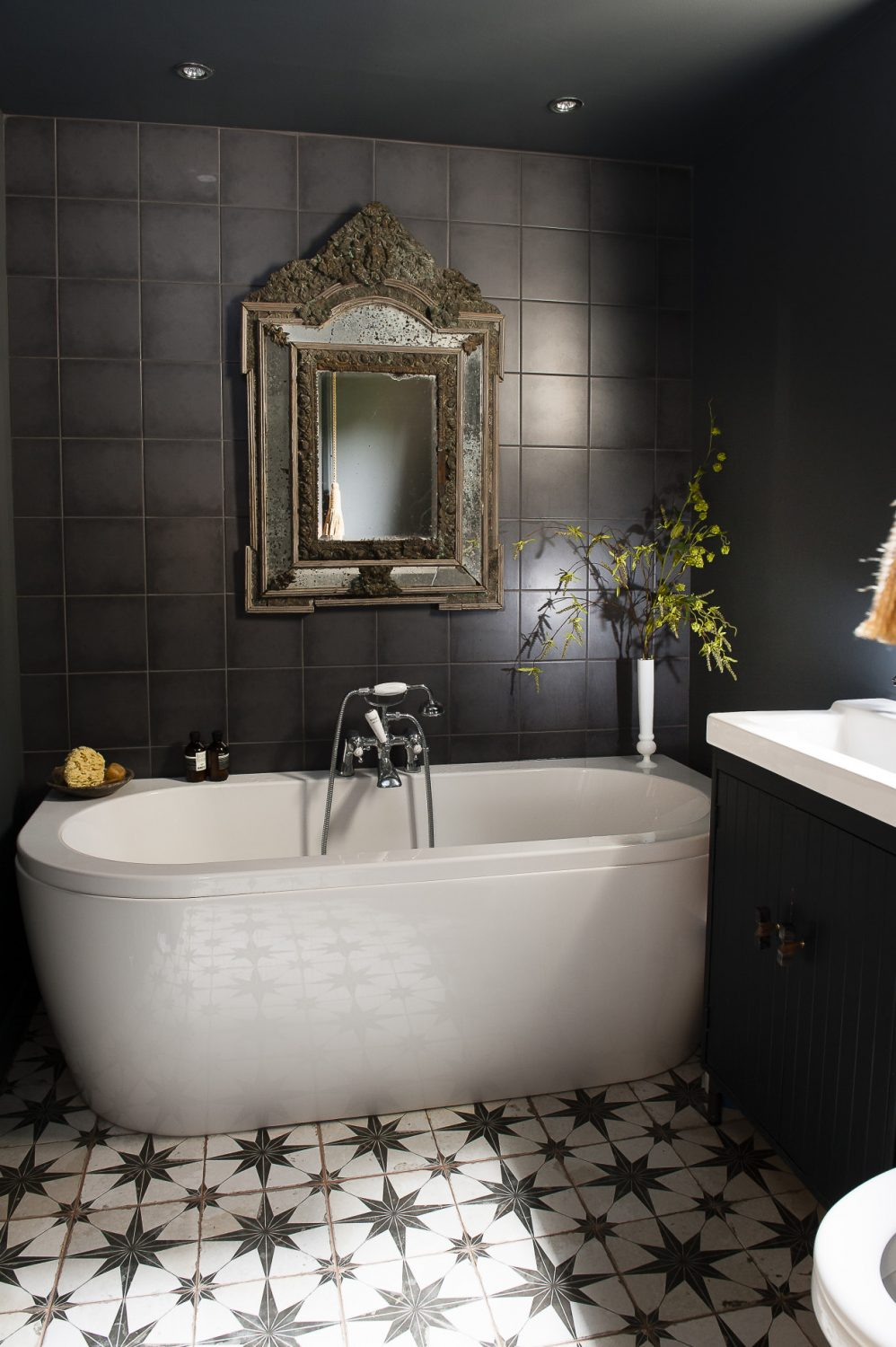 Featuring a deep contemporary oval bath with a central hand shower, star design floor tiles on the characteristic bold scale, plus a basin atop a black painted unit, the bathroom, while relatively small, packs just as much dramatic punch as the rest of the flat.