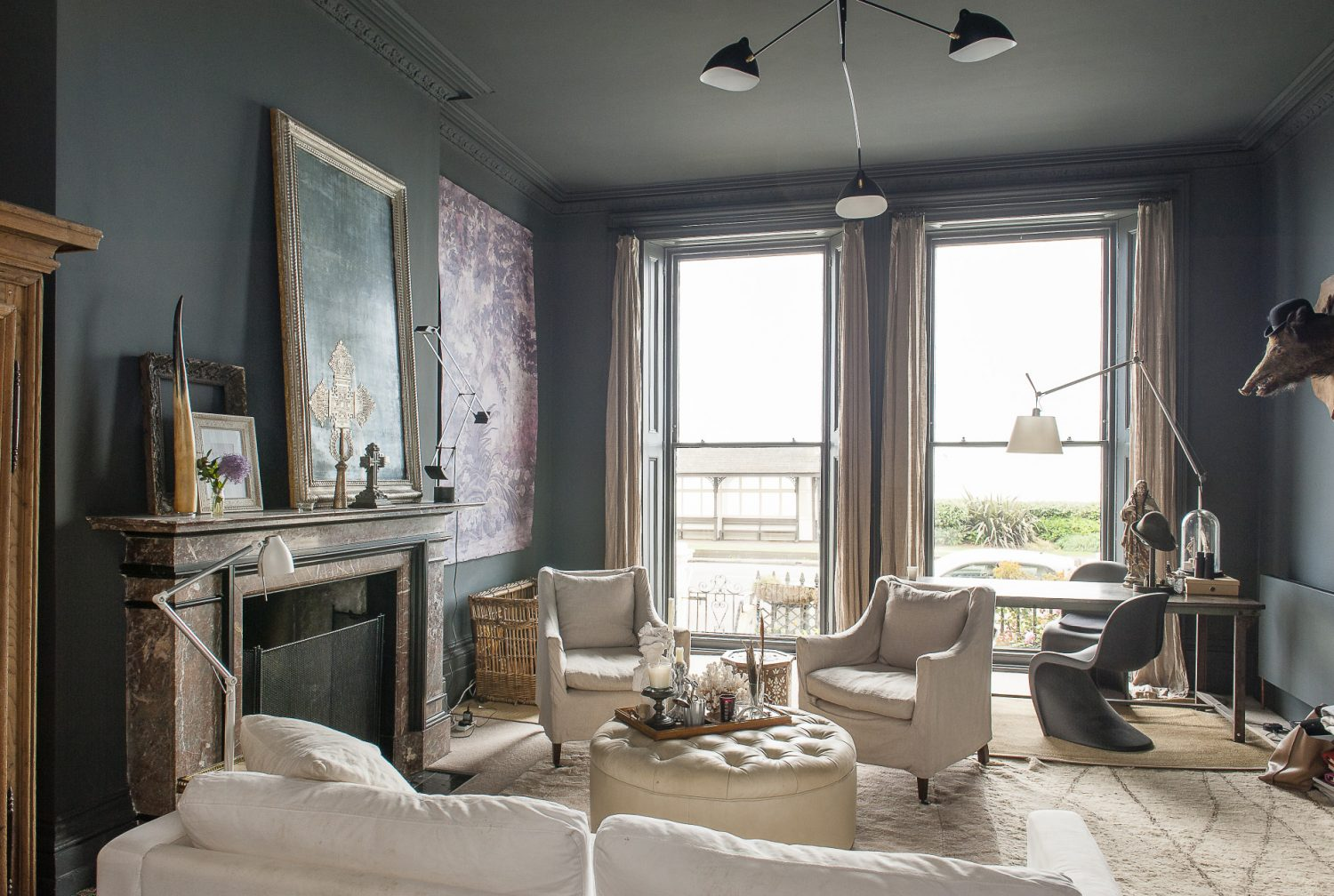 The striking drawing room features wonderfully large windows which span the full length from floor to ceiling