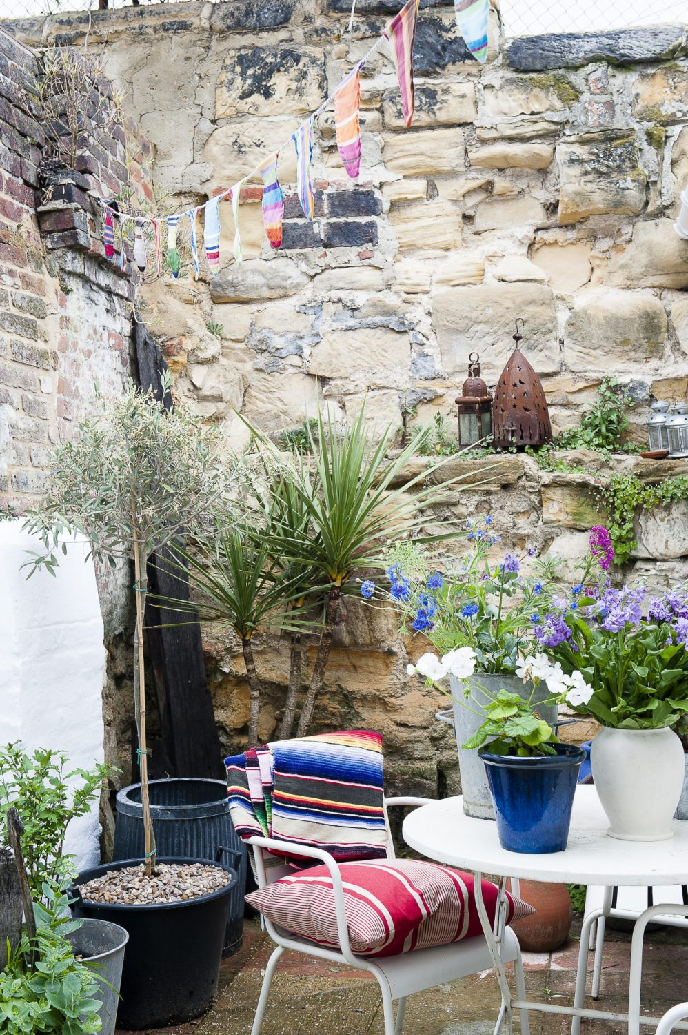 Double doors open out from the sitting room into the courtyard where Helen has decorated the space with driftwood and pebbles and bunting from SHOP