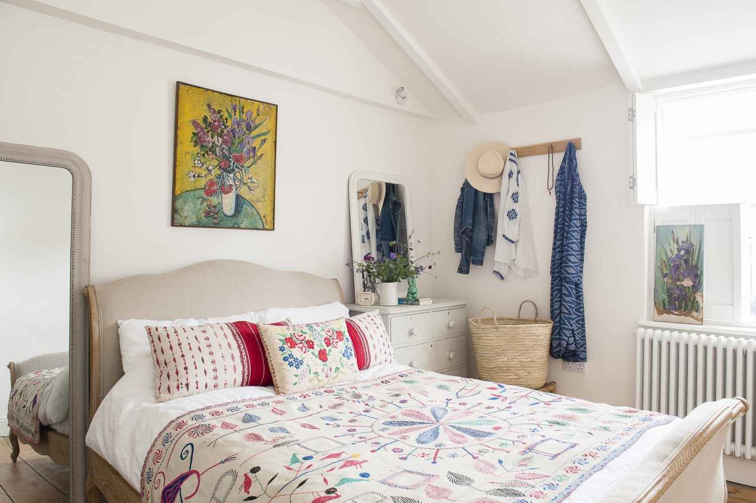 Helen's bedroom is a gloriously pared back 'homage to a Greek bedroom', with white walls and shutters, a bed by Loaf, an Indian quilt and Romanian cushion and paintings from a fellow Norman Road trader