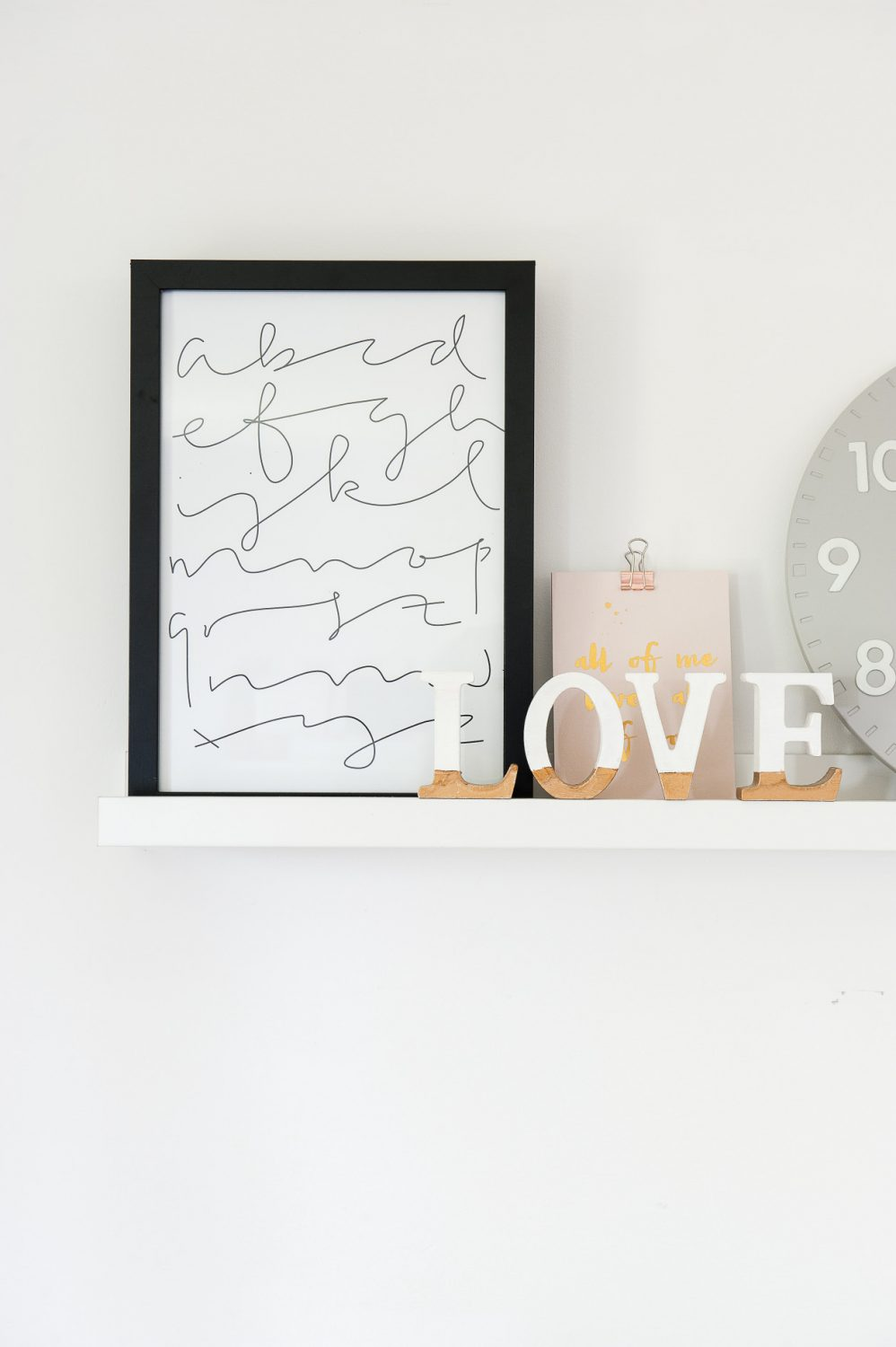 Groupings of prints and objects line shelves along the walls and above the bed
