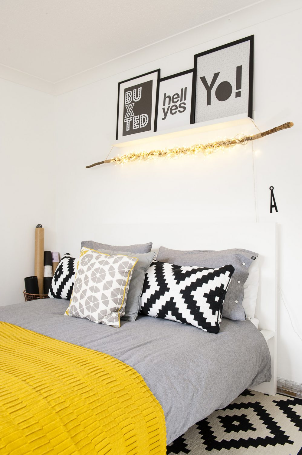 """I tend to switch things round a bit in here. The yellow throw and bedding is from Homesense, the geometric cushion is from Made.com and these cushions are from IKEA to match the rug on the floor."""