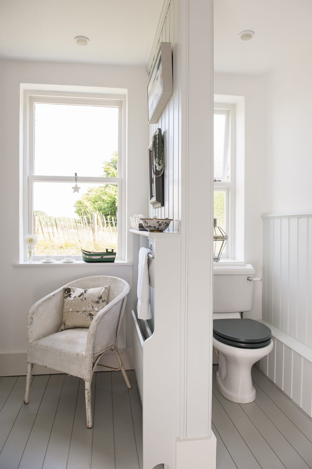 The bathroom features a soft, sea coloured scheme with shells and beach finds arranged on shelves and windowsills. The loo is partitioned away from the bath area, making it separate, but still part of the room