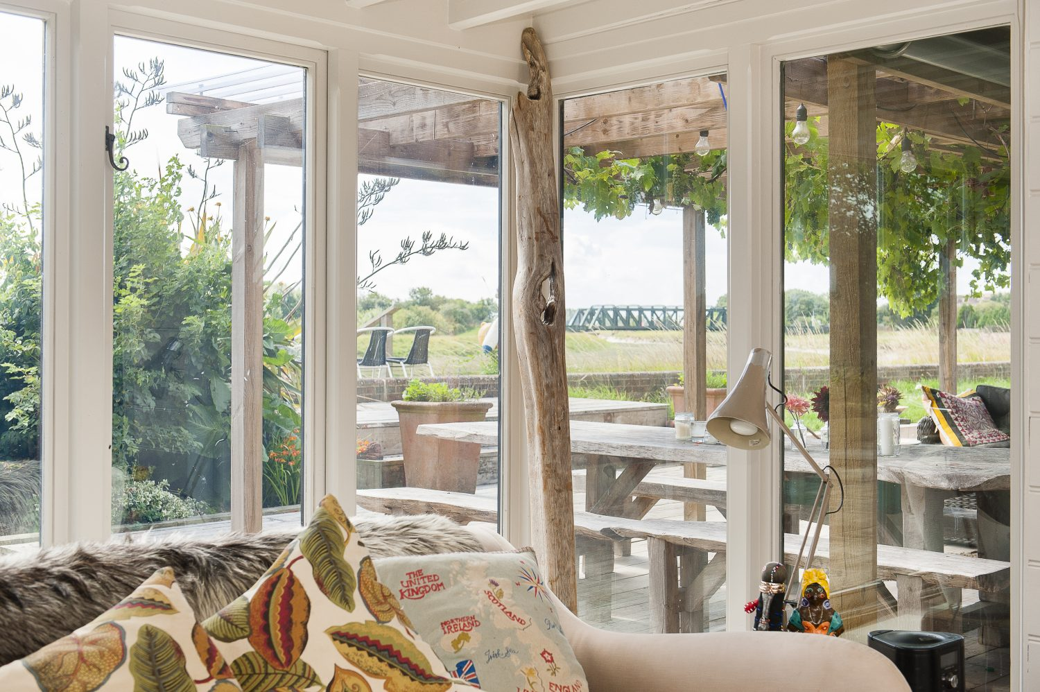 Glass doors lead out from the sitting room and dining area onto a deck shaded by a pergola
