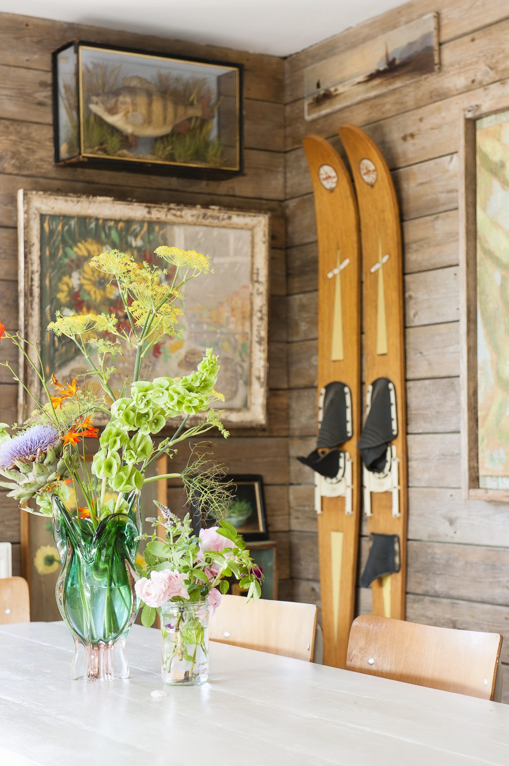 In contrast to the bedrooms, the dining room features cladding running horizontally rather than vertically along the internal walls. A life ring and vintage water skis allude to the property's river setting