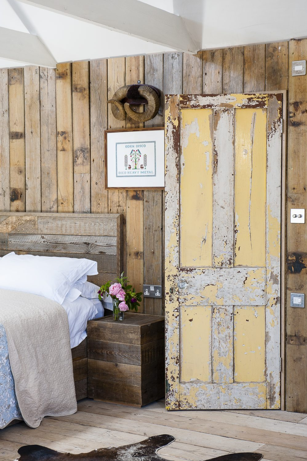 Crisp white ceilings and floral bedlinen are the perfect foil for the rustic reclaimed wooden flooring and panelling in one bedroom