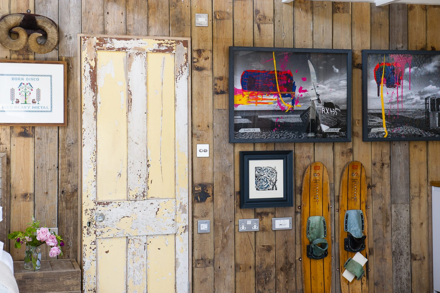 More of John's artworks, made in collaboration with artist Luke Hannam, hang in a downstairs bedroom above a pair of vintage water skis