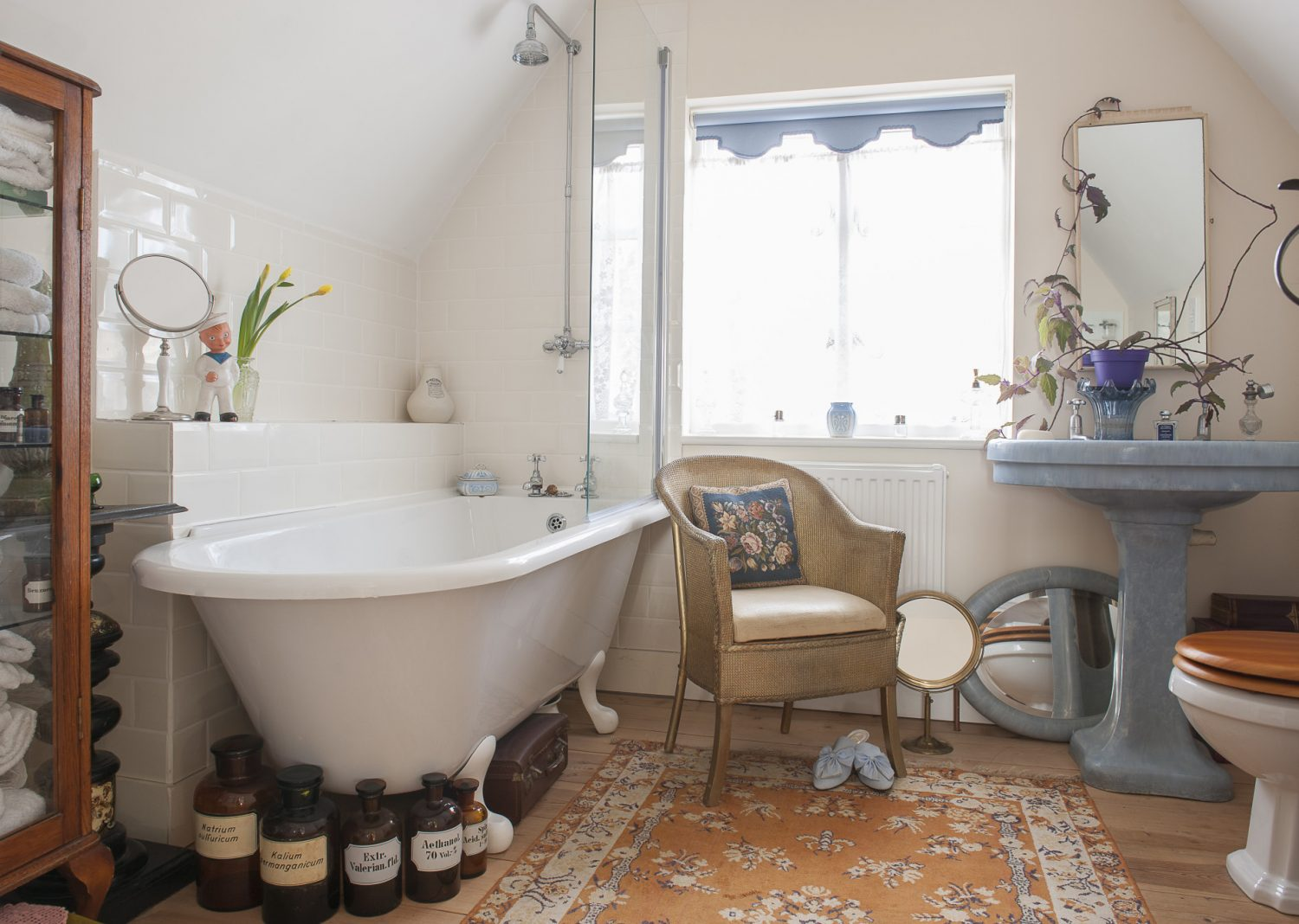 The bathroom features an amazing bright blue 1920s washbasin – not actually plumbed in, but too beautiful to leave in the second-hand yard in Hastings Old Town. Its vibrant colour is matched by a pair of pale blue grosgrain mule slippers Adrian couldn't resist from Fortnum & Mason
