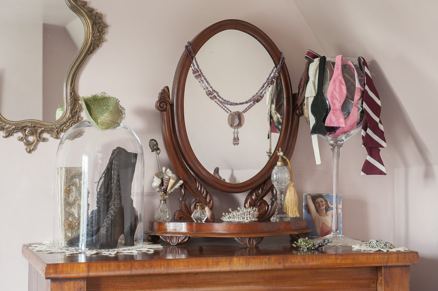 The two guest rooms, in the original south side of the house, are packed with more found treasures. In the pink bedroom, hat pins, hat boxes, Victorian laced boots, tiaras and bow ties share space on top of a chest of drawers