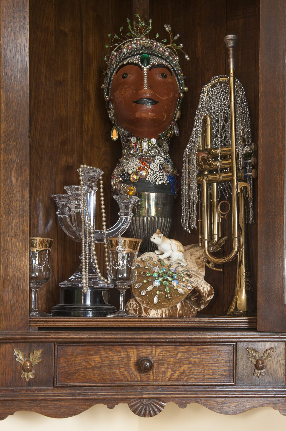 Adrian embellished the vintage wig stand with hundreds of crystals, sequins and buttons. He had the trumpet as a boy
