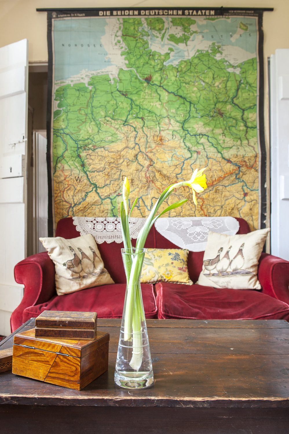 A vintage school map of Germany hangs over a sofa that used to belong to Adrian's parents