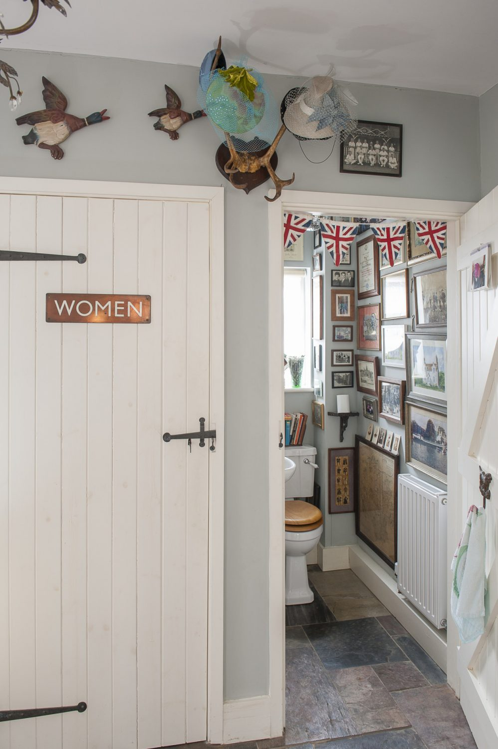 The walls of the downstairs loo are covered with framed photographs, prints, cards and letters with personal meaning