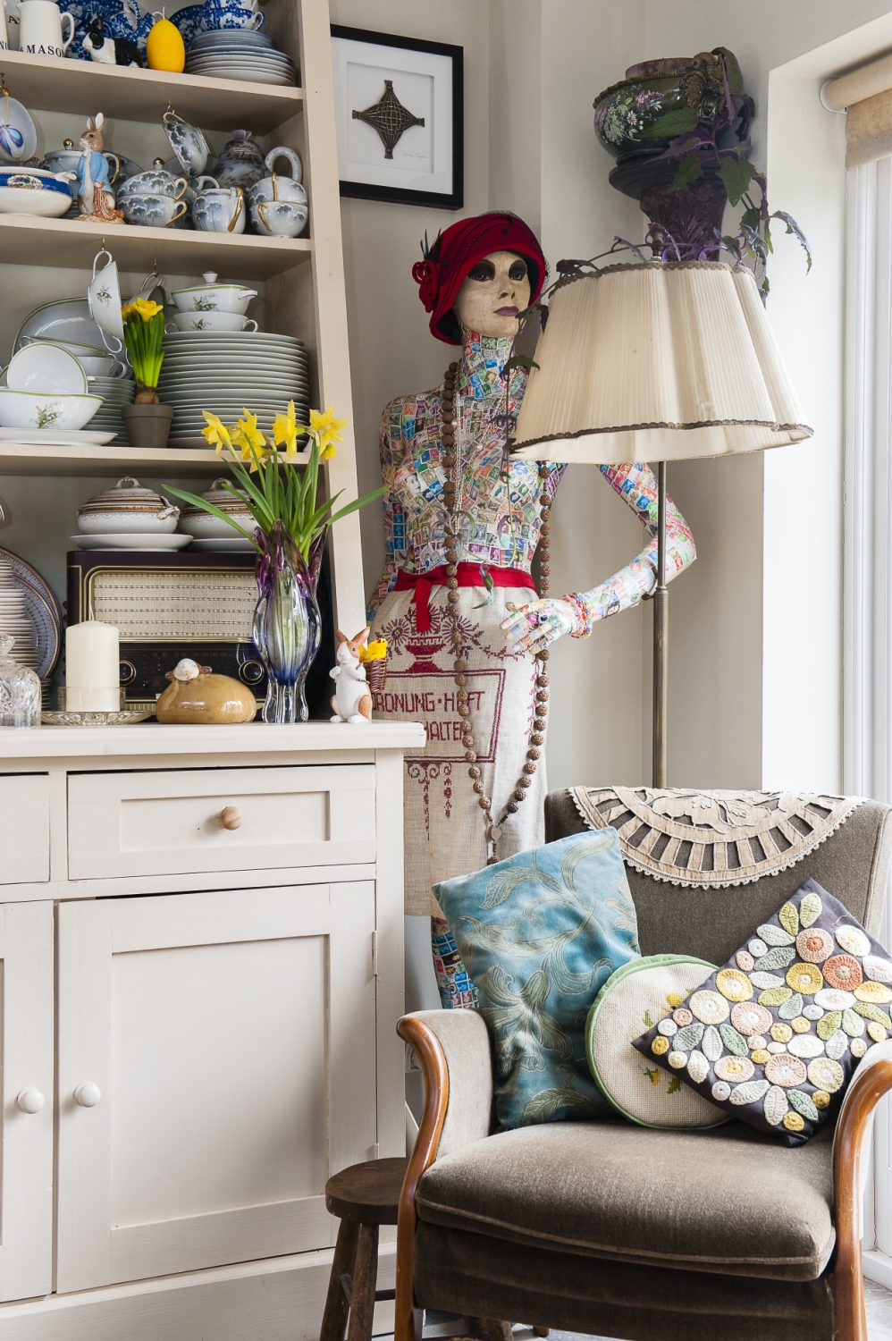 Gladys the mannequin stands in one corner of the kitchen wearing a chic red cloche hat, made by Adrian