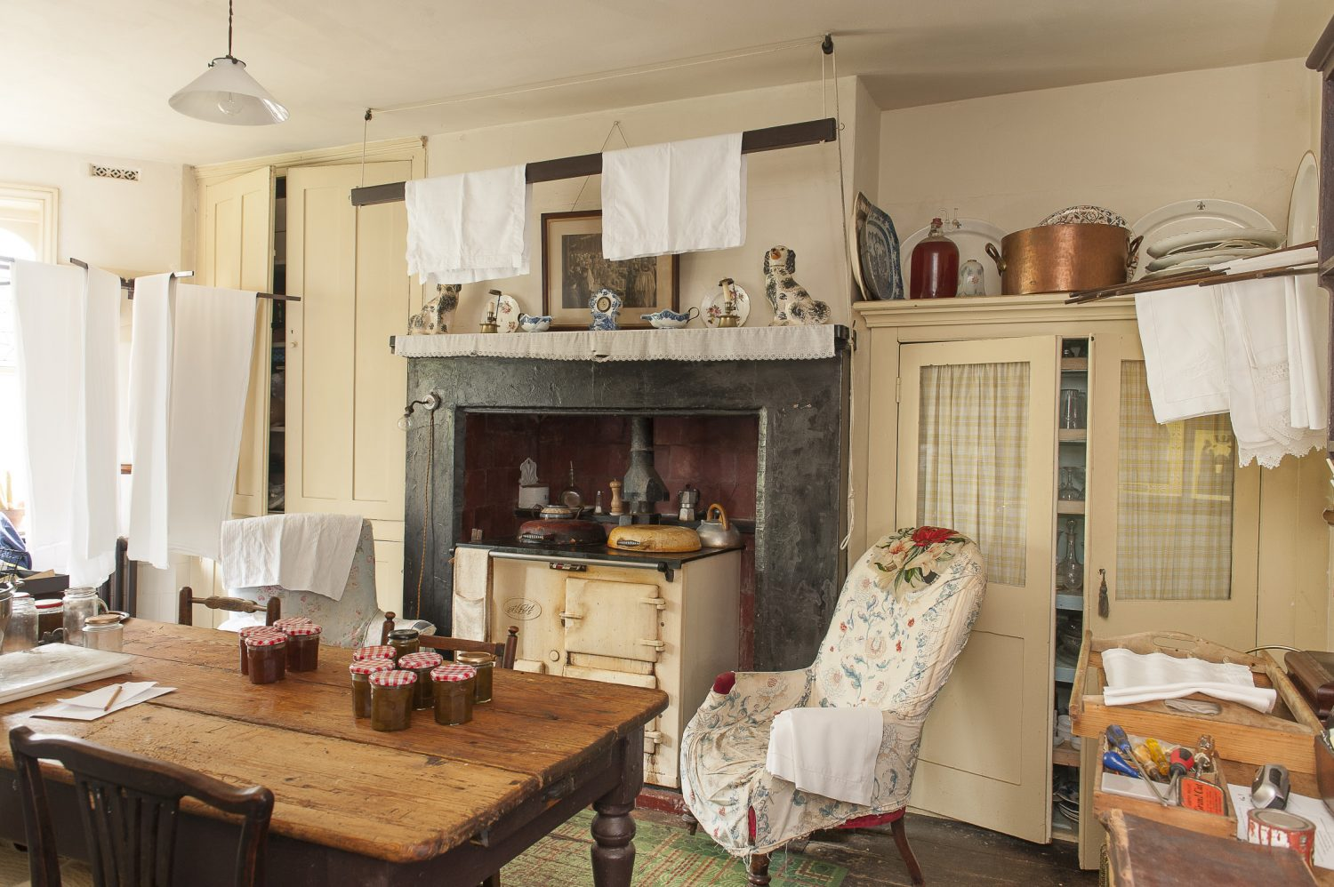 In the large kitchen, ironed cotton sheets hang on wooden hoist and spindle airers