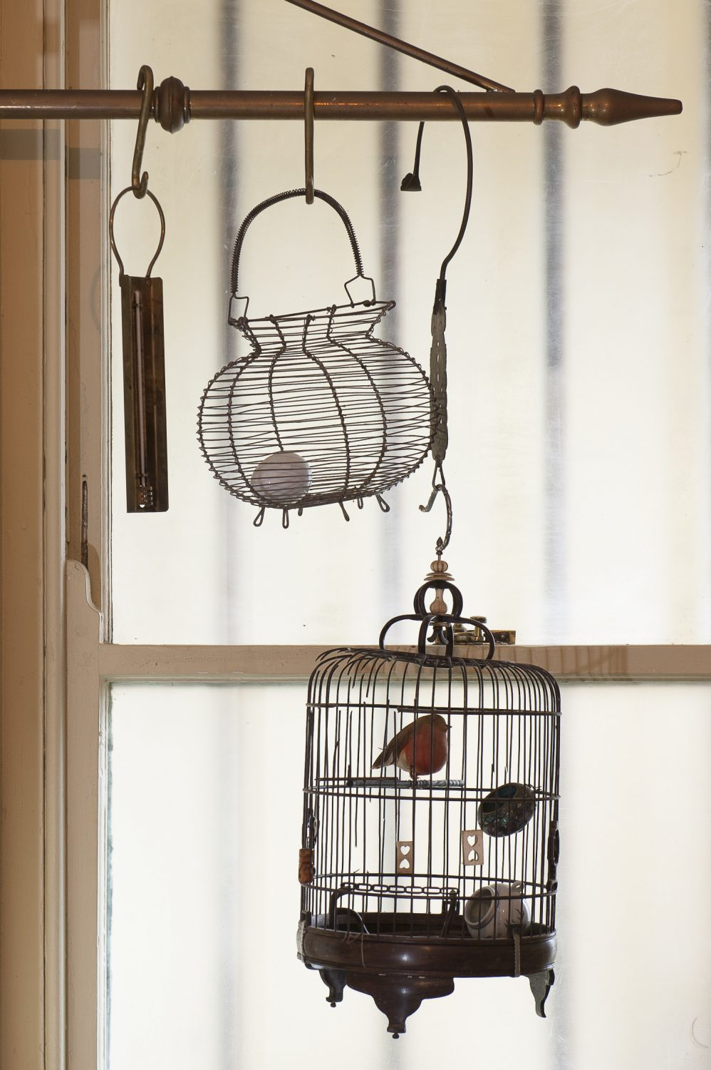 A decorative birdcage hangs in the kitchen