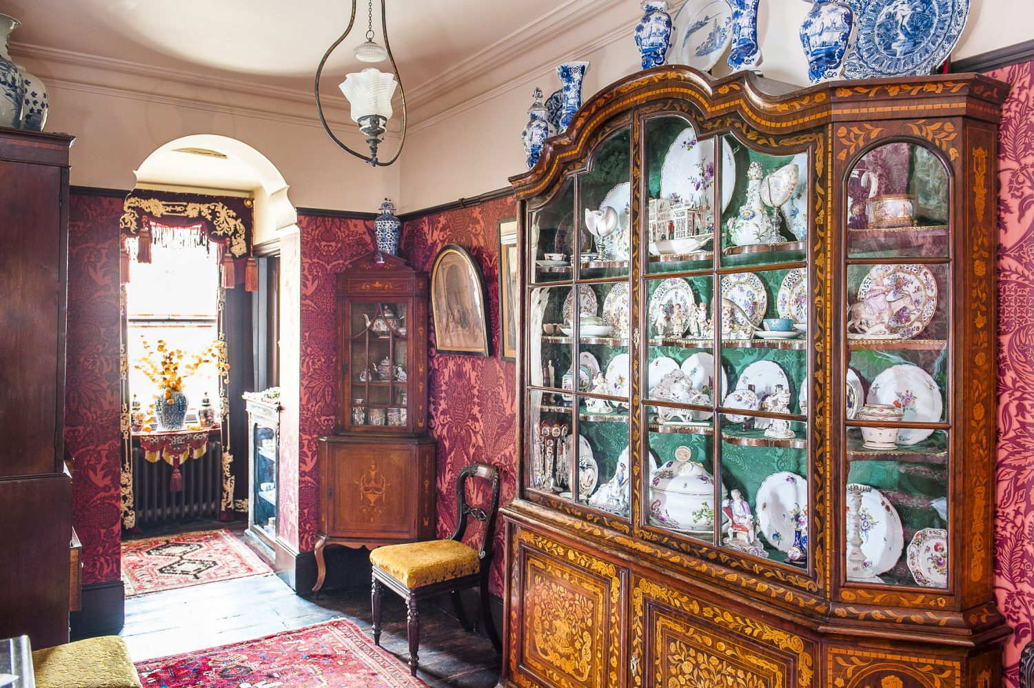 A collection of chinaware is displayed in an ornate cabinet