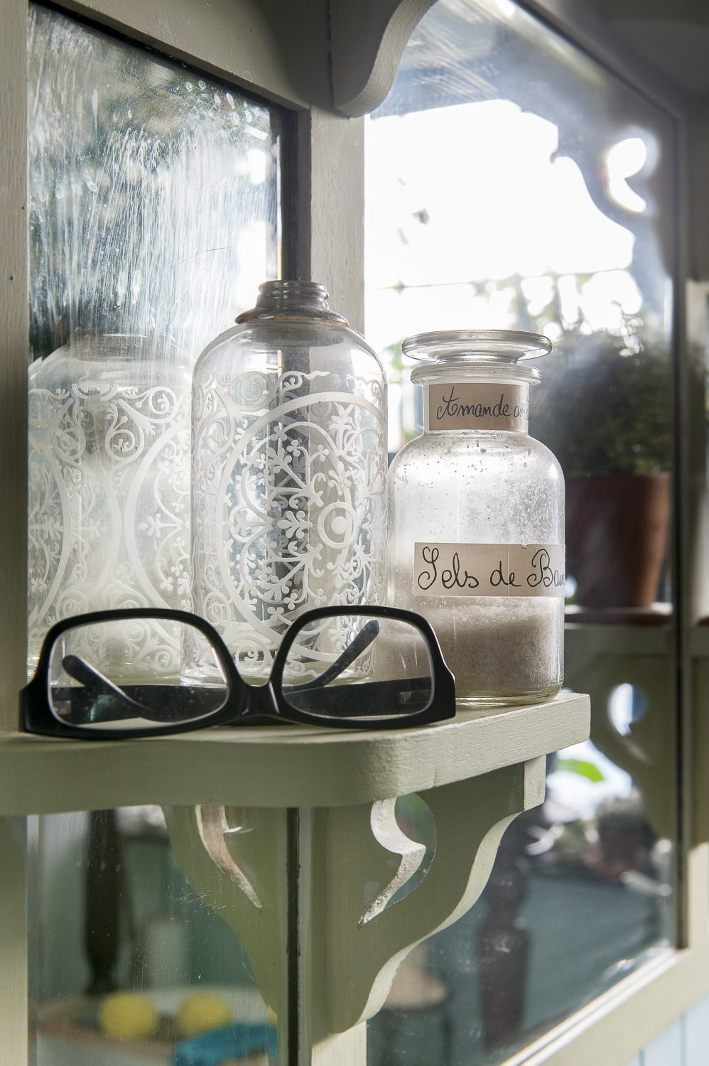 Decorative apothecary bottles line the shelves surrounding the bathroom mirror