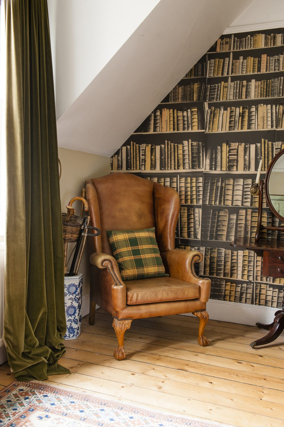 One upstairs bedroom has a complementary masculine feel, with the air of a gentleman's club in the leather chair, velvet curtains, horse painting and the 'New Antique Books' wallpaper by St Leonard-based wallpaper designer Deborah Bowness.