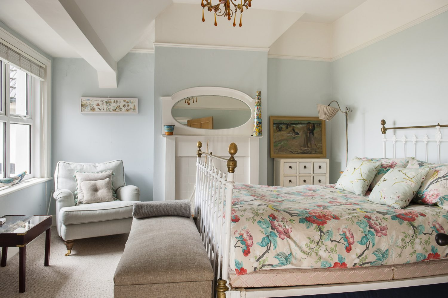 The front bedroom of the upstairs flat is very light and feminine, with a white fireplace and over mantle mirror, a lovely old brass bed and a temptingly squashy armchair