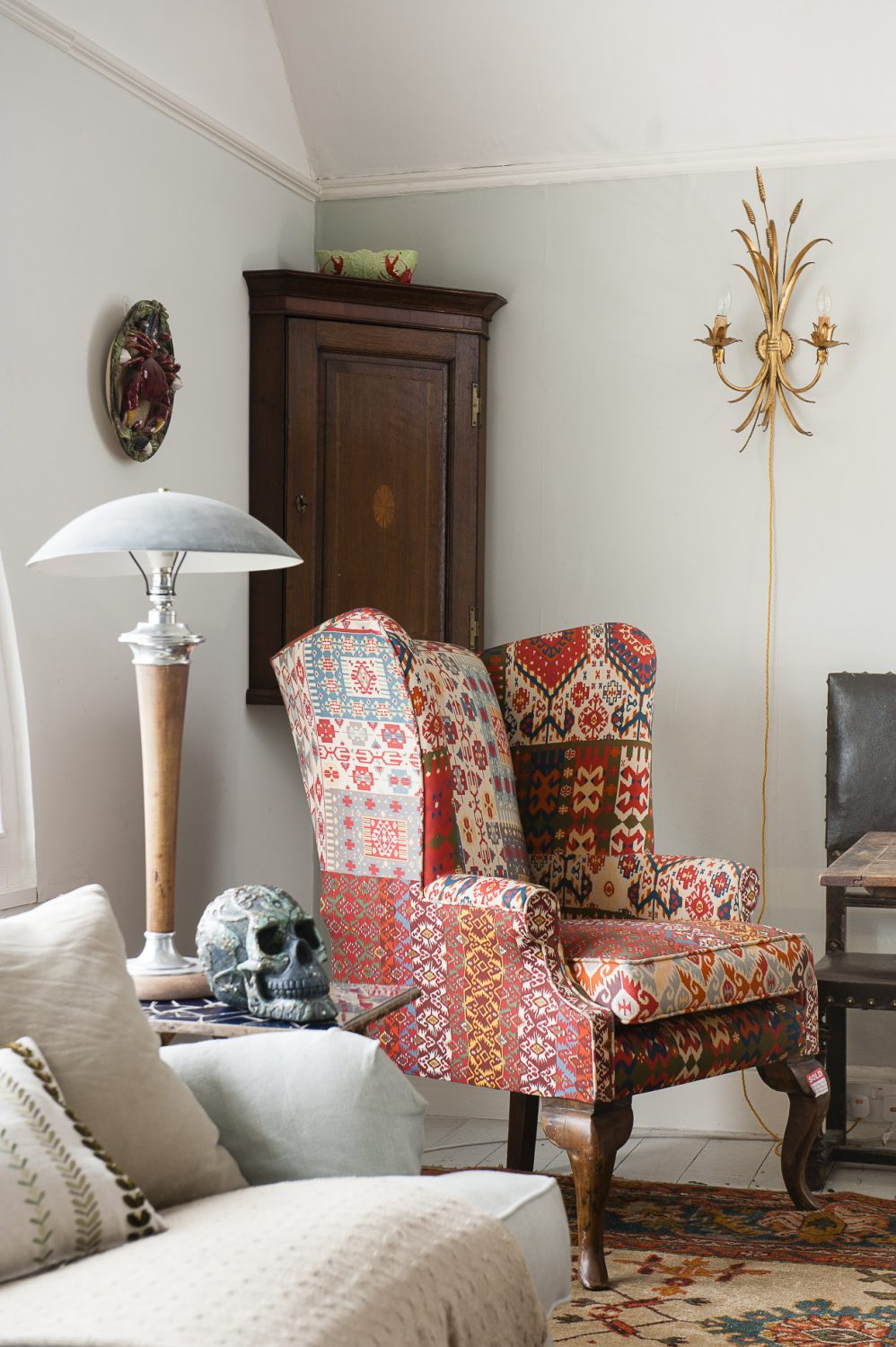 An armchair upholstered in a patchwork of Ikat provides the perfect place to sink into after a day at the seaside