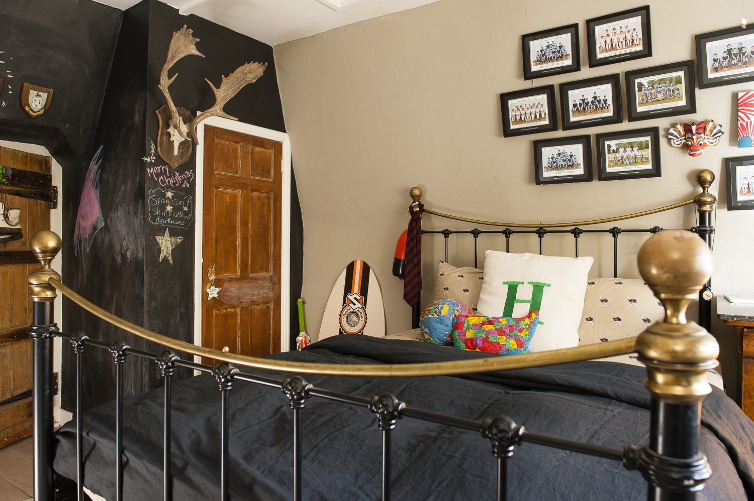 A pair of stag's horns loom down from a dramatic (and very useful) blackboard wall in one of Kali's sons' room