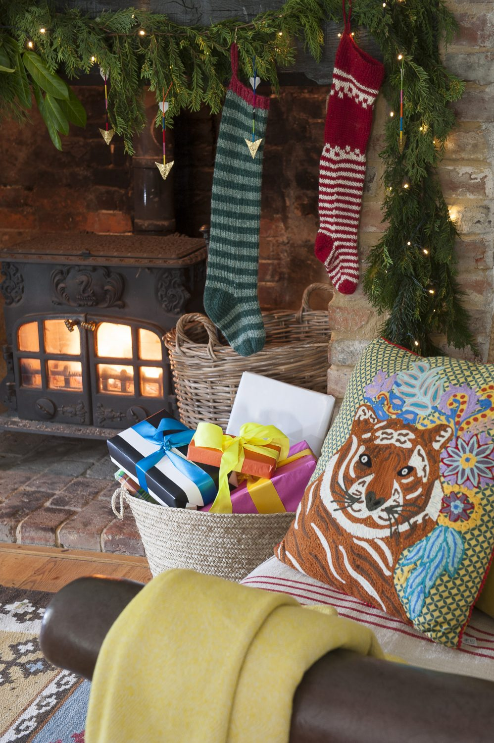 Presents lie wrapped in woven baskets beside the cosy woodburning stove