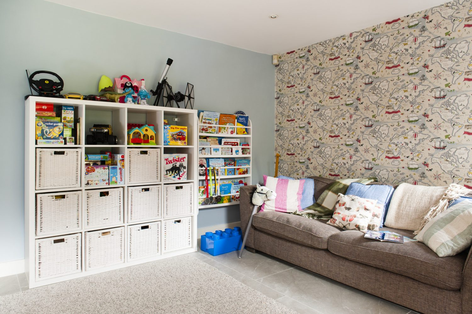 A door off the dining room leads into the children's playroom, with a comfy sofa, plenty of toy storage and one wall of map of the world wallpaper