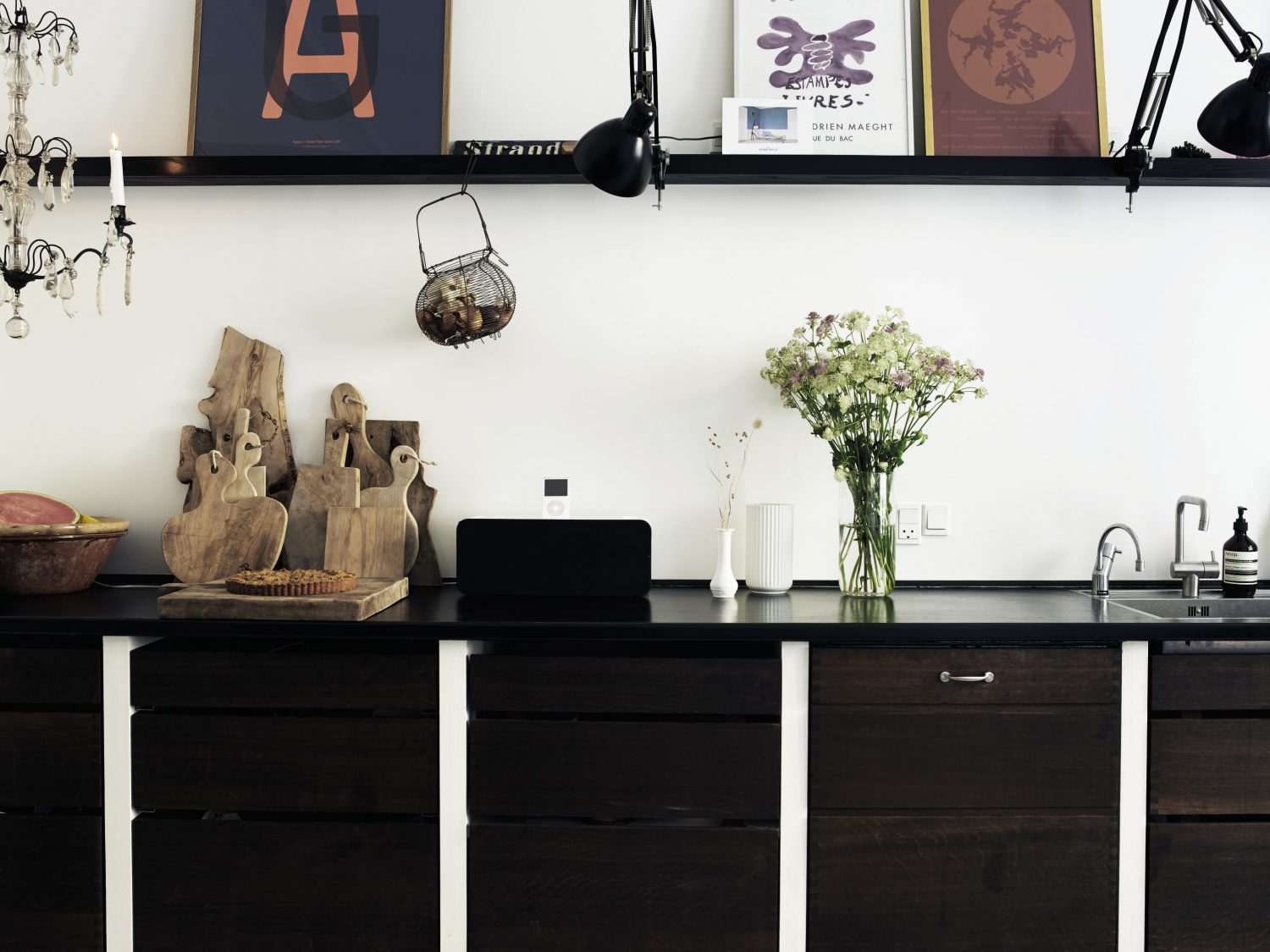 In the kitchen, dark wood cabinets run along one wall and there are no wall cabinets. Instead, a long black shelf is used as an opportunity to display pictutes and objects. A group of olive wood chopping boards on the work surface add a welcome organic touch.