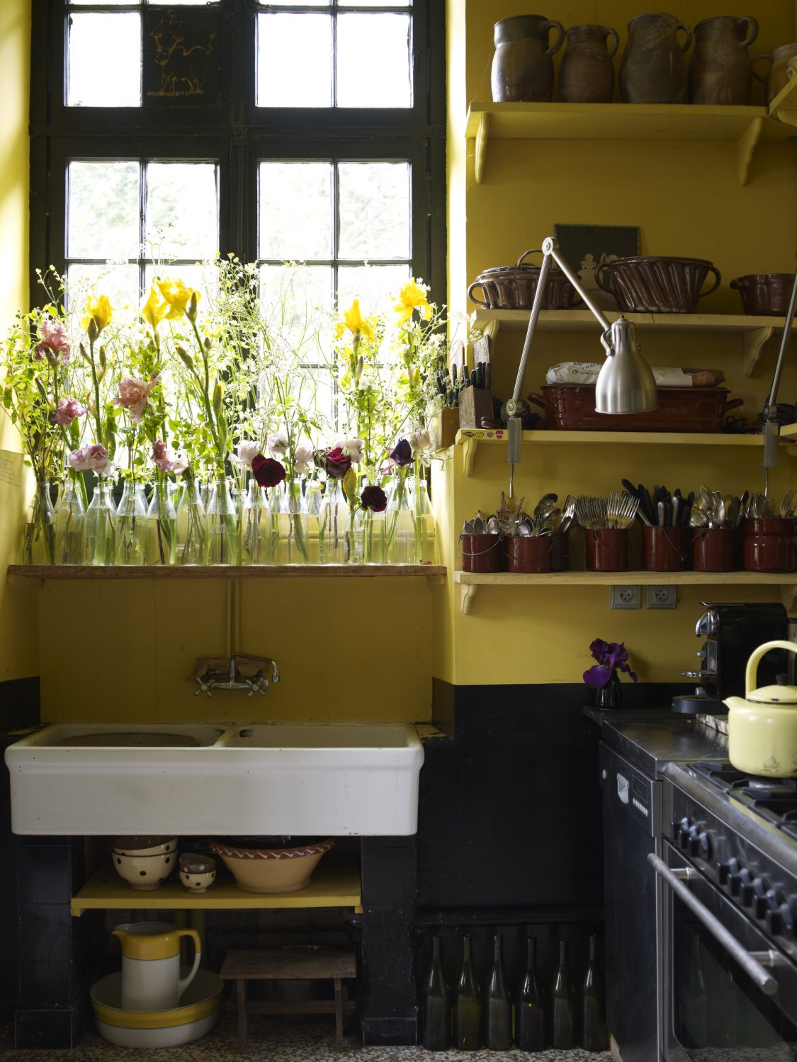 Country Kitchen: In the home of artist Claire Basler, flowers are in abundance. Above the old vintage butler's sink, blooms line up in re-employed grocery bottles. In brown enamel containers, she's stacked her vintage silverware, found at market places, while a lemon yellow teapot resides on the hob. Claire shows off twists of must-have modernity, like the coffee machine and an industrial-style light to assist with food preparation.