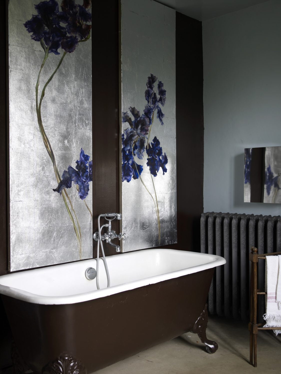 Old World Comforts: In Claire Basler's bathroom, she has a generously sized vintage claw foot bathtub. Her trademark giant floral paintings, in this case irises on a silver canvas, provide a beautiful backdrop to bathe by. Linen towels hang from an old towel rail, heated by a shapely antique radiator.