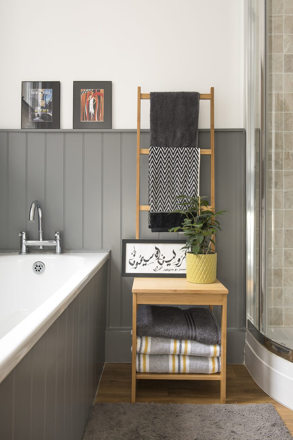 Along the corridor, the family bathroom is a tranquil haven of greys peppered with yellows and whites