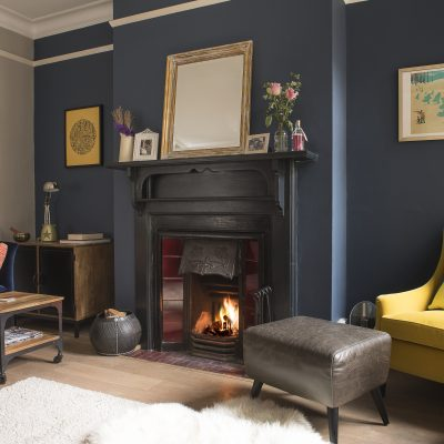 Next to the kitchen is a cosy room known as 'the snug'. Initially a very light grey, and devoid of much natural light, Caroline has worked with the darkness, choosing deep tones and adding little pops of colour
