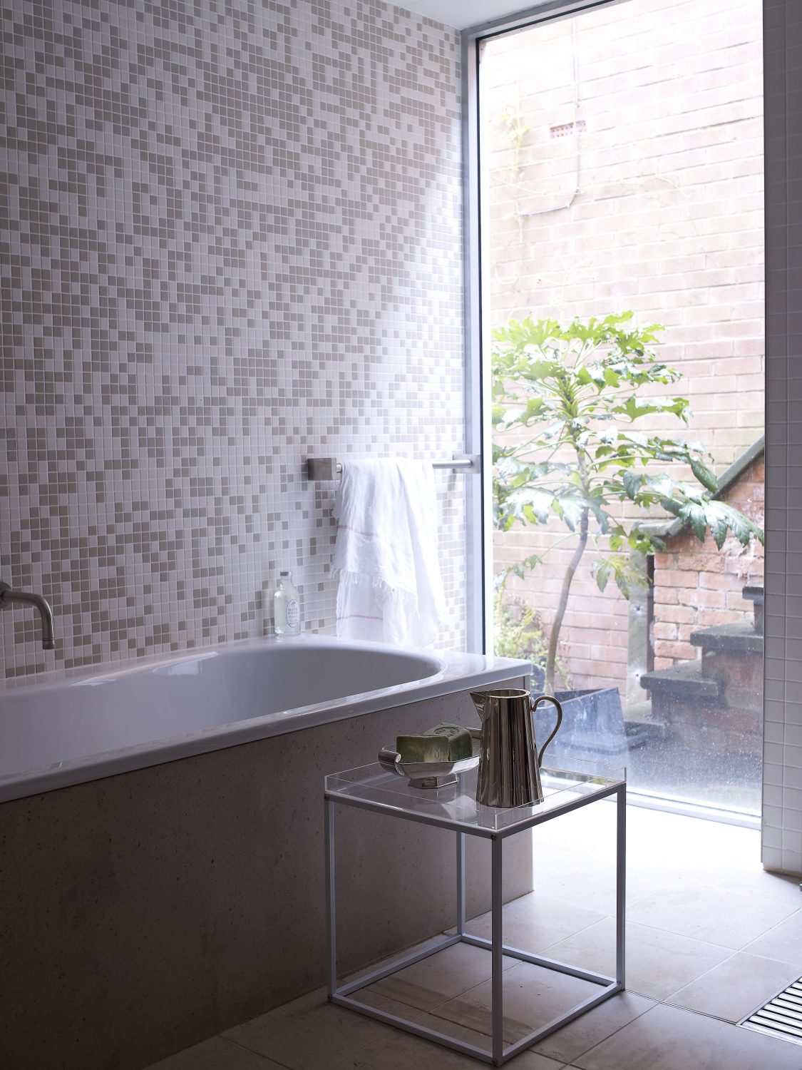 Reincarnate Key Pieces: An elegant, modern, square-legged side table becomes a practical bathing aid in Tim Rundle's bathroom. On top, a vintage silver jug and soap dish reside, adding glinting, pretty accessories. Here, tiles play with proportion: large square floor tiles juxtapose with the tiny taupe and white mosaic tiles on the walls. The bath, painted in taupe, continues the natural, neutral feel. The large floor-to-ceiling window brings in the natural world, making this the perfect urban space in which to relax and reflect.