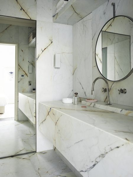 In the bathroom, the walls are clad in giant slabs of dramatically veined marble. More marble forms an innovative sink unit, where water drains away via a discreet horizontal slot