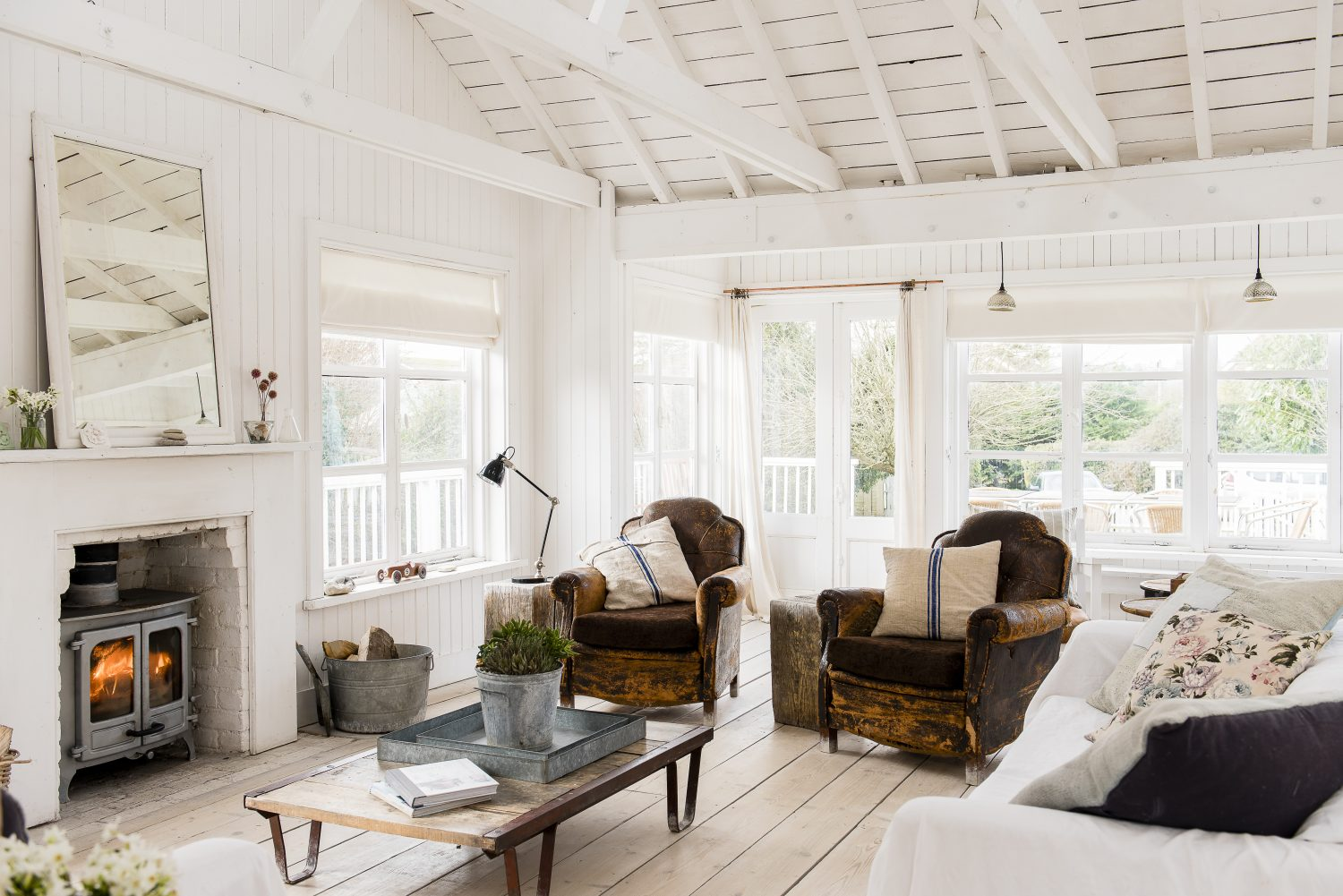Looking out onto the deck and into the garden, with light pouring in from all sides. The gloriously patina-ed club chairs and the cushions – made from grain sacks –are all from Pale & Interesting. The flowing curtains – the essence of a summery beach house feel – are antique linen sheets