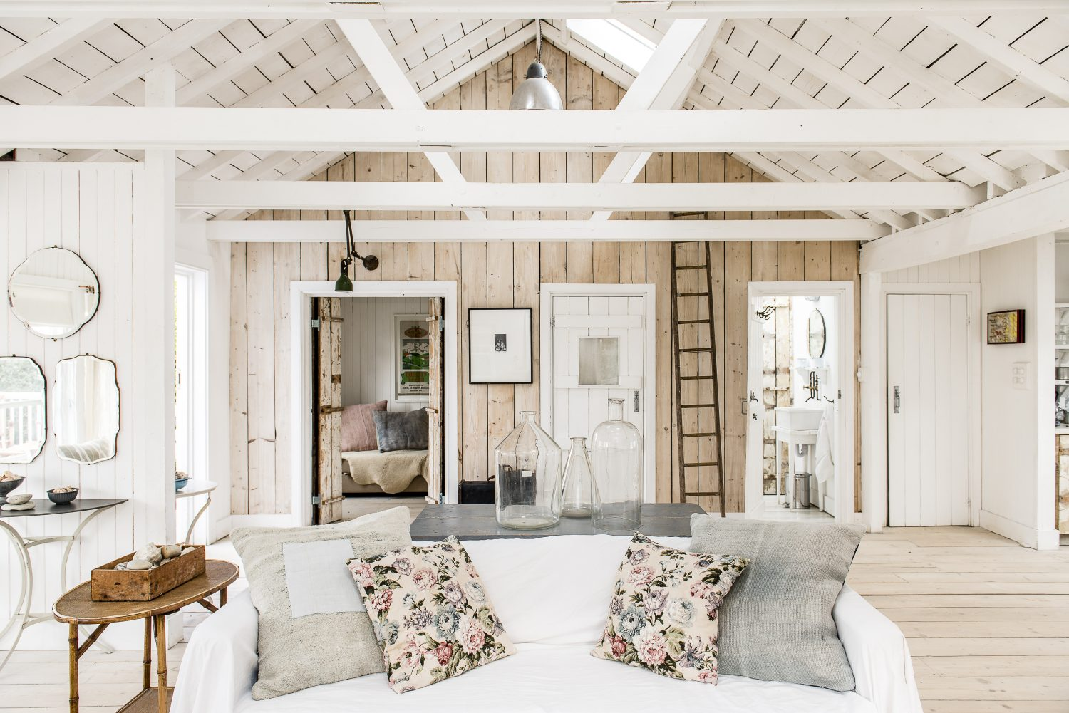 Atlanta and Dave removed the original ceilings to expose a double height, pitched ceiling and open up the cabin, to create one central living space. The floors throughout are old scaffolding planks sanded and treated with a special Danish finish and several applications of white soap